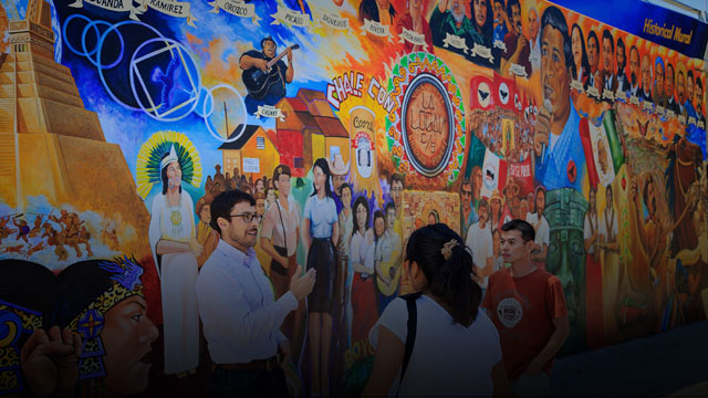 students standing in front of colorful mural
