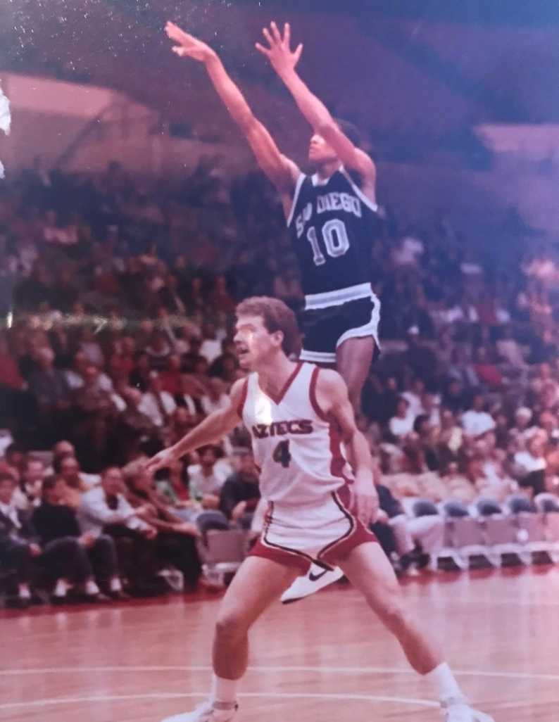 Chris Carr '86 playing on the court in a USD vs SDSU basketball game