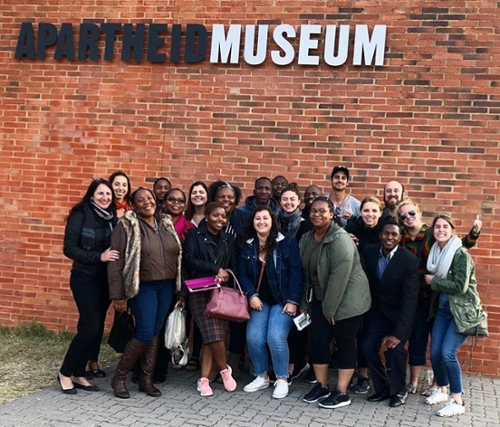 students posing in front of the Apartheid Museum