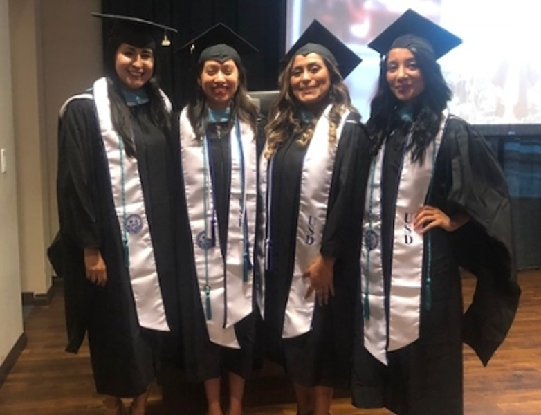 four students in graduation gowns