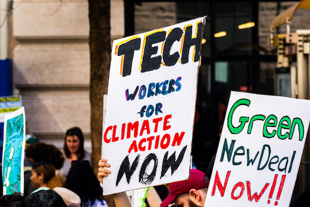 "Protest signs that read ""Tech workers for climate action now"" and ""Green new deal now"""
