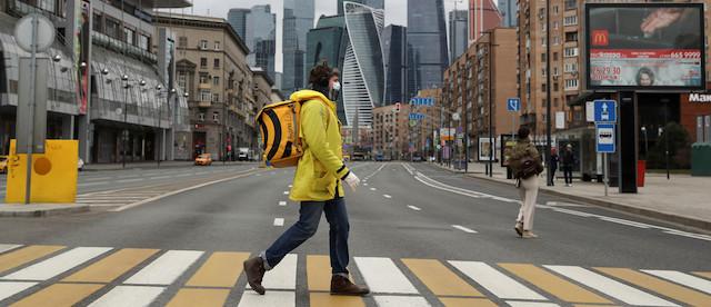 man walking in city wearing a mask