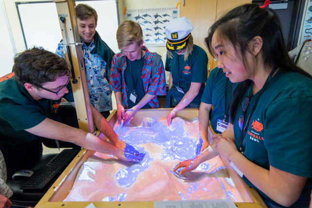 EOSC senior Nicole Yamada shows high school students the augmented reality sandbox.