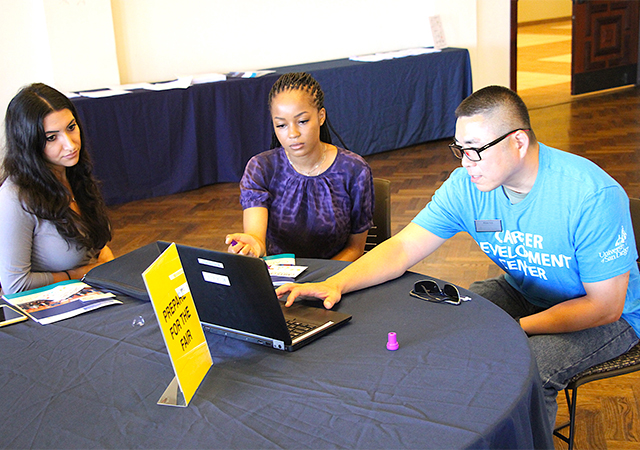 Career Development Center 's Alex Lo, far right, works with students during Tuesday's Career Cafe event in the UC Forums.