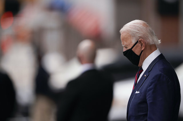 Image of Joe Biden wearing a mask, head down preparing for a speech