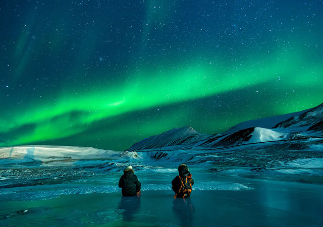 image of two people undearneath the aurora borealis
