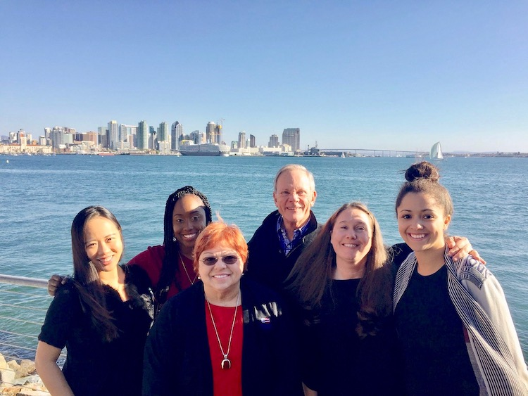 USD alumna and founder of the Reshoring Institute, Rosemary Coates, stands in front of San Diego Bay with USD grad students and SCMI director, Joel Sutherland