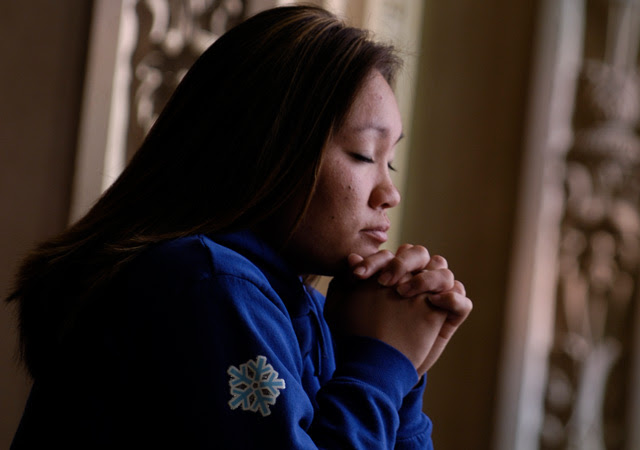 one woman praying with eyes closed