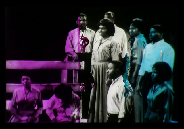 Video still from An Ecstatic Experience. Purple, white and blue washed over a black and white image of a black actors on stage.