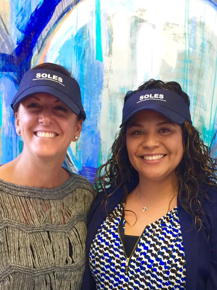 image of Kacey and SOLES alumni director wearing SOLES visors