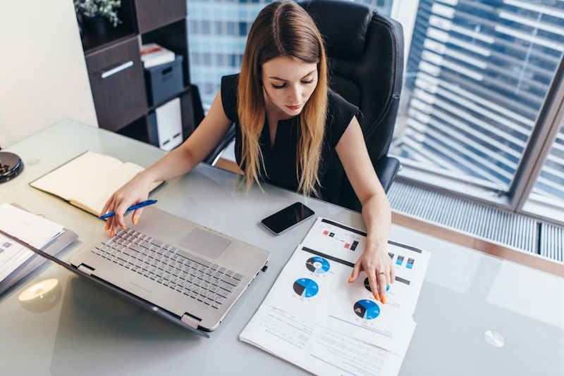 A female business analyst sits at desk in front of laptop looking at printed pie charts showing data.