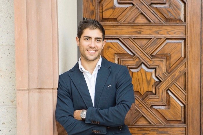 USD MBA alumnus, David Jimenez Burgos, poses in front of a door on campus