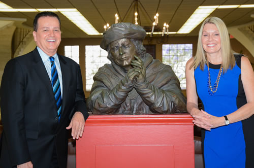 USD Professors of Business Law, Craig Barkacs and Linda Barkacs pose next to a statue