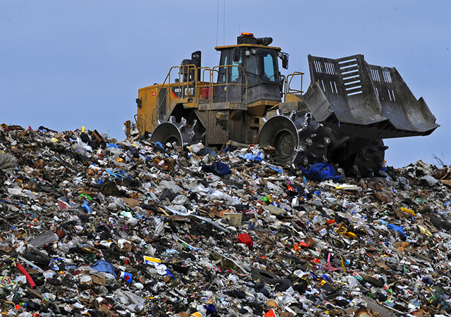 Tractor driving through landfill