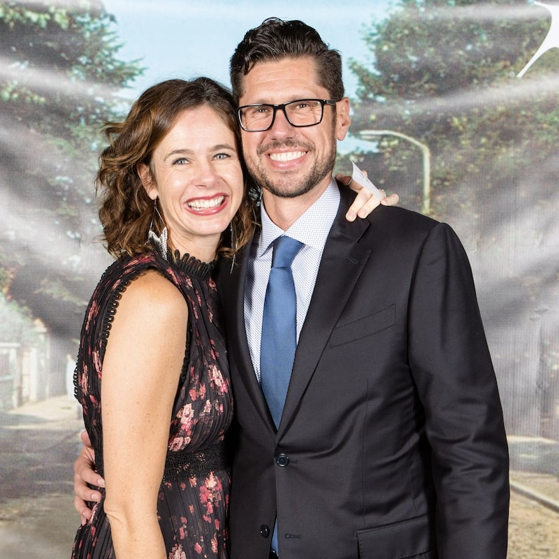 University of San Diego alumni, Lauri Brennan '95 and Bill Brennan '96, hug in front a screen featuring a tree-lined street