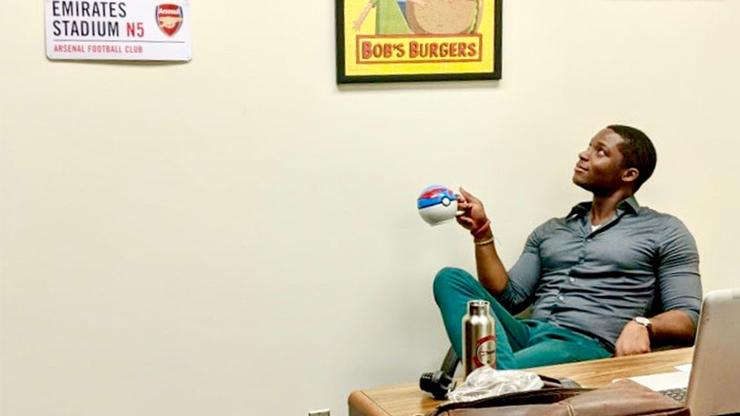 USD School of Business Assistant Professor of Economics Jason Campbell sits in his office chair looking up at his memorabilia of FC Barcelona soccer gear and Bob's Burgers poster