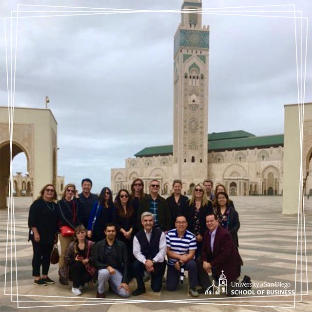 USD School of Business faculty pose in front of a mosque's tower in Casablanca, Morocco