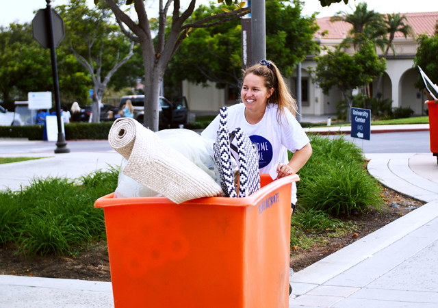 Student pushes a cart toward her residence hall during move-in day at USD.