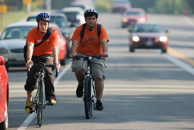 Two men biking amongst traffic