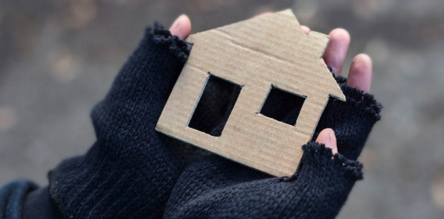 image of hands holding a house made of cardboard
