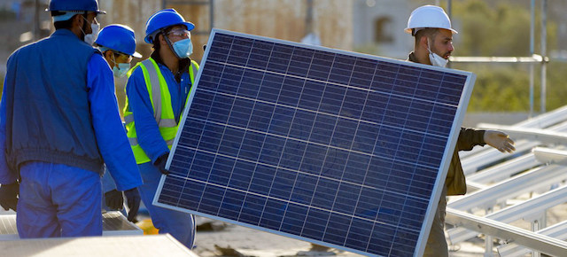 Construction workers carrying a solar panel