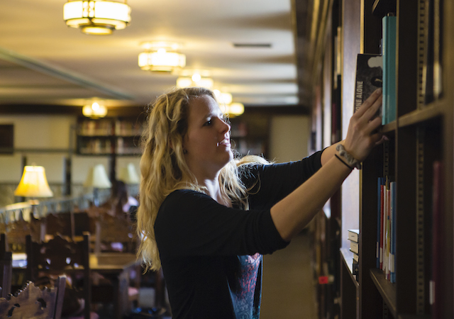 student pulling books off shelf Copley Library