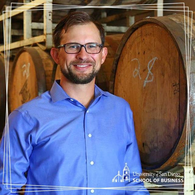 USD alumnus, Bryan Carpenter, BAC '07 posing in front of beer barrels
