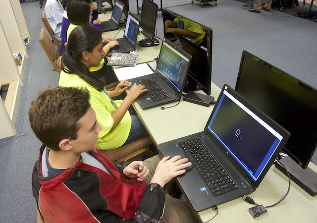 Cybersecurity students at laptops