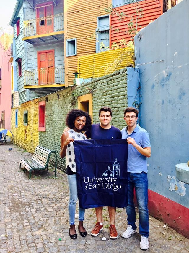 USD students holding up a USD banner in a colorful neighborhood of Buenos Aires, Argentina