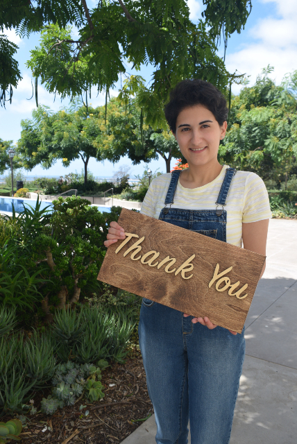 Kroc School student holding thank you sign