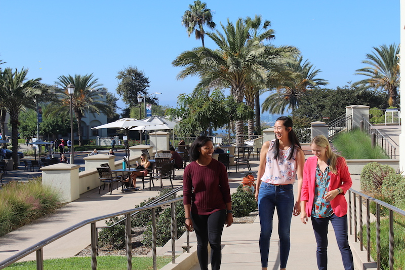 A black woman, asian woman, and white woman walk together at University of San Diego campus