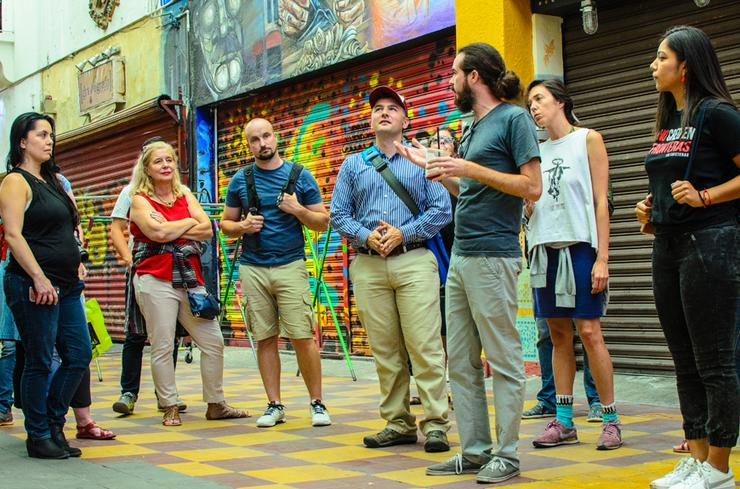 TransBorder Institute Director Ev Meade, center, and certificate program students visit Pasaje Rodriguez with Luis Montijo (third from right).