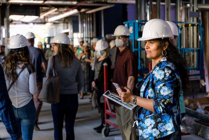 USD Associate Dean and Professor, Priya Kannan, leads business alumni along a hard hat tour of Knauss Center for Business Education