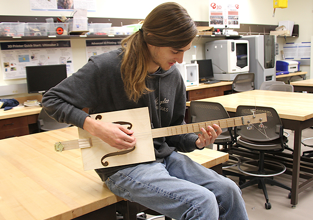 Engineering student strums a cigar-box shaped guitar that he made in an Acoustics of Musical Instruments course.