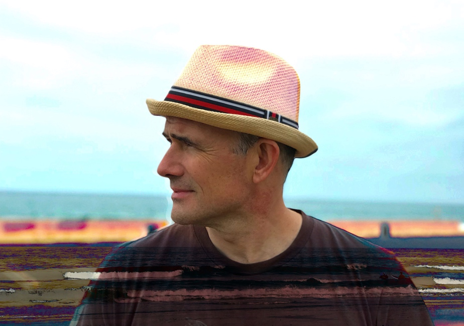 side portrait view of Danielewski wearing a straw hat with an abstract colored background