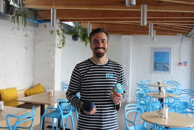 Man smiling holding reusable coffee cups