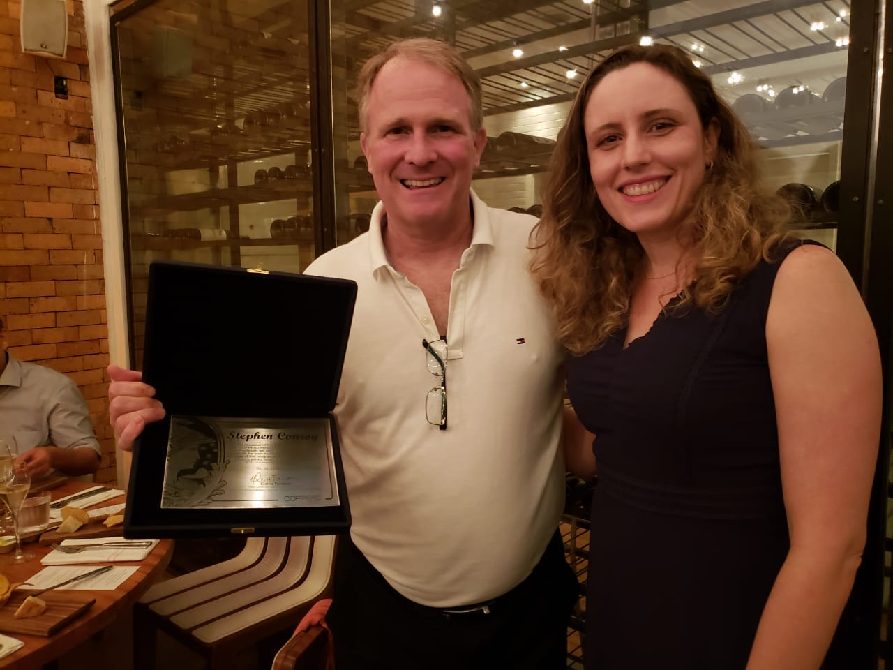 Dr. Stephen Conroy accepts a plaque at COPPEAD in Rio