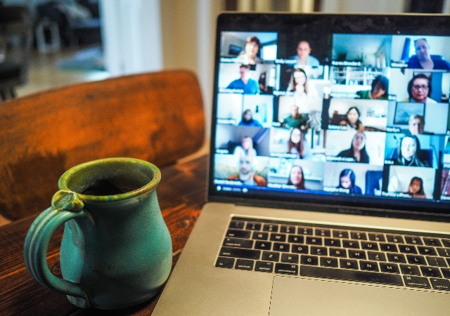 a zoom call with many people on a laptop computer next to a coffee cup