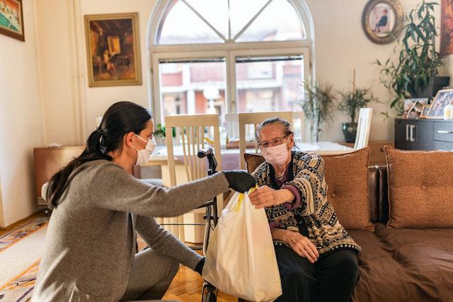 Volunteer in mask providing food to homebound senior