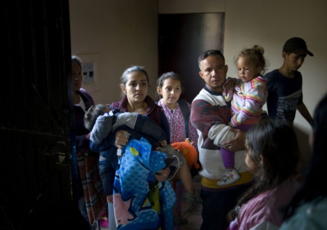 A family from Honduras, center, waits to be received at a migrant shelter in Tijuana, Mexico in April