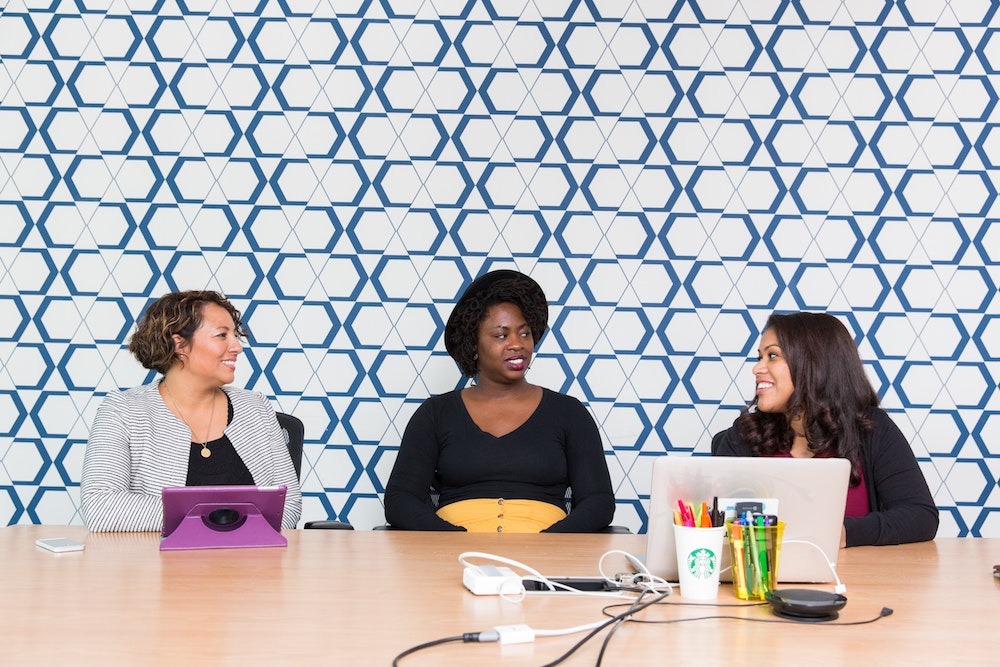 Diverse women discuss business at a table