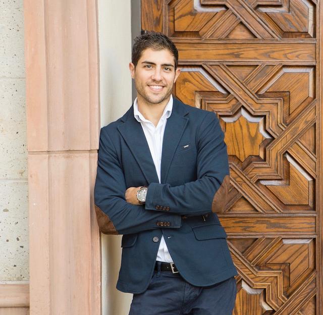 USD MBA alumnus, David Jimenez Burgos, poses in front of a door on campus