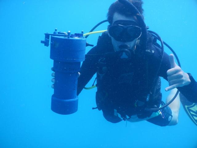 Stephen underwater with a scientific instrument in scuba gear.