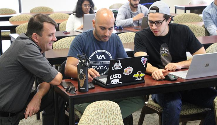 Students work together on a class assignment for the USD School of Business Master of Science in Business Analytics degree program.