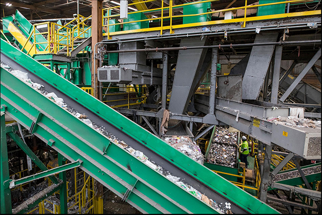 Mixed plastics are conveyed toward an optical sorter at a recycling plant