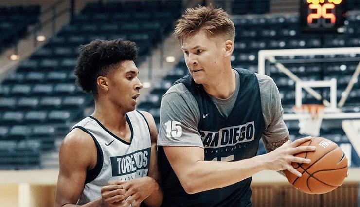 The lone senior player on the USD men's basketball team, Alex Floresca, right, works in practice. The team opens the 2019-20 season at 7 p.m. Tuesday at home against UC Irvine.