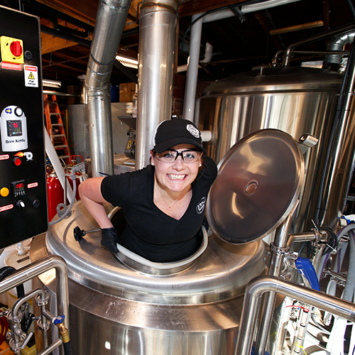 USD alumna Stephanie Eppig popping out of a barrel at her brewery, Eppig Brewery