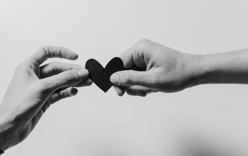 a hand passing a heart to another hand