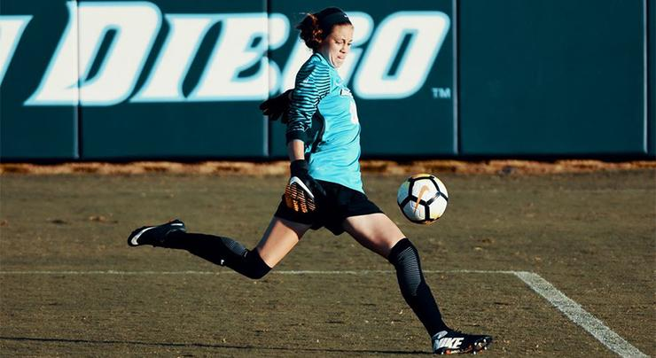USD women's soccer goalie Amber Michel kicks a ball.