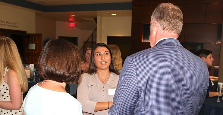 Lissette Vasquez, an Industrial and Systems Engineering major, shares her internship story at U.S. Postal Service with Jamey Power, right, during a Summer Internship Award reception.